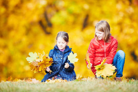Children playing with leaves at autumn park