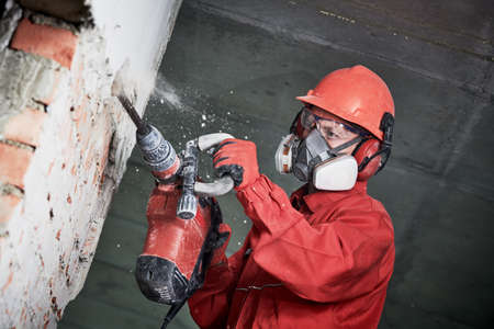 worker with demolition hammer breaking interior wall Stock Photo