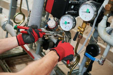 heating engineer or plumber in boiler room installing pipeline manometer Stock Photo