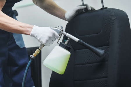 Seat upholstery cleaning with high pressure air pulse cleaning gun Stock Photo