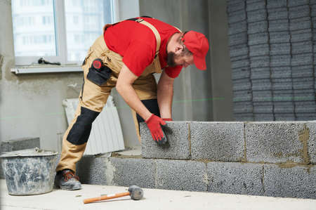 bricklayer working with ceramsite concrete blocks. Walling