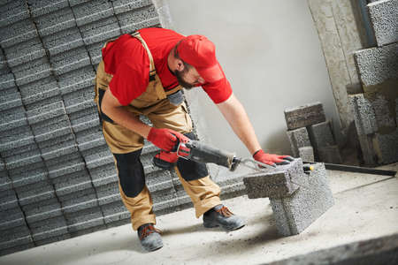 bricklayer cutting ceramsite concrete blockswith saw at walling Stock Photo