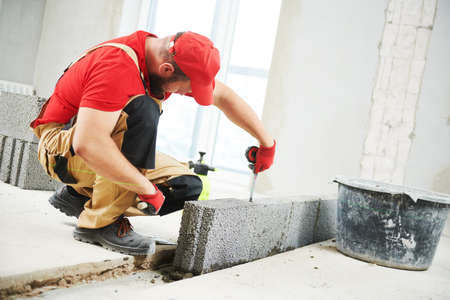 bricklayer builder working with ceramsite concrete blocks. Walling