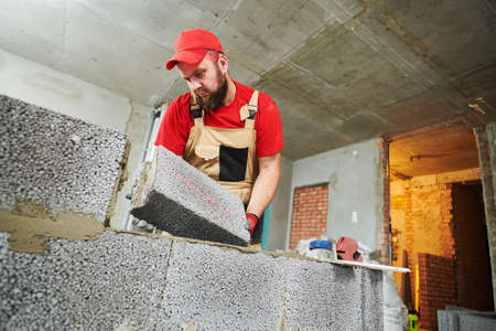 bricklayer working with ceramsite concrete blocks. Walling Stock Photo - 152824441