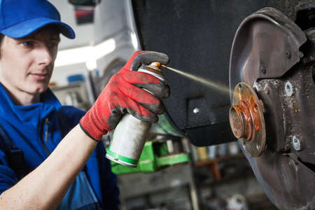 Automobile service. Lubricating car hub while disk and brake pads replacement in repair shop or garage