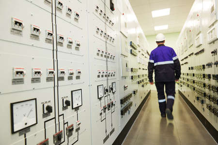 industrial worker at power energy supply factory. Focus on fusebox