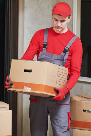 Moving or delivery service. Mover worker carrying cardboard boxes into home Reklamní fotografie