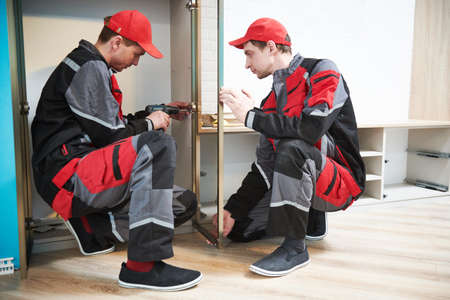 Furniture assembling. Professional worker installing cabinet at living room of new house. Stock Photo - 159032429