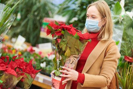 woman in mask buying flowers for domestic gardening in shop at coronavirus lockdown.