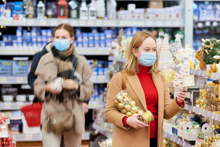 woman in mask buying new year decoration in shop at coronavirus lockdown.