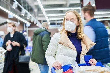 woman in mask buying food in shop at coronavirus epidemic Stock Photo