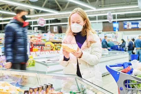 woman in mask and protective gloves buying food in shop at coronavirus epidemic