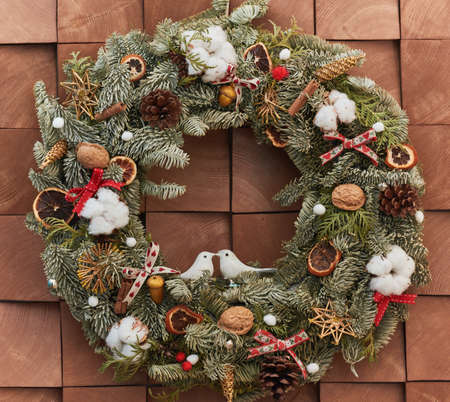 festive Christmas wreath with decorations on wall