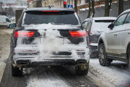 City winter snowfall. Car covered with snow driving on street Stock Photo