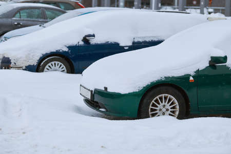 Car covered with snow in winter on city street during snowfall. Stock Photo