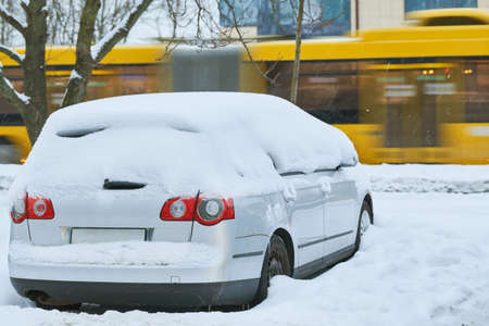 City winter snowfall. Car covered with snow on street
