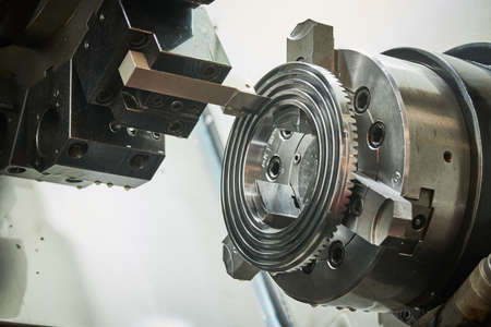 turning operation on cnc machine in metalworking industry. Cutting tool makes spiral groove on metal detail face Banque d'images