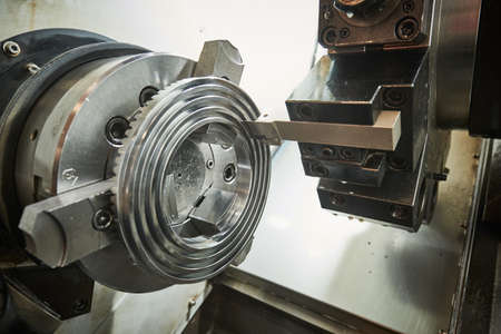 turning operation on cnc machine in metalworking industry. Cutting tool makes spiral groove on metal detail face