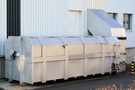 shrinking: An external thru-the-wall compactor at the backyard of a shopping center. It is used to compact carton paper and corrugated board boxes.