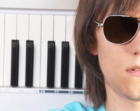 Portrait of young man in sunglasses with piano, isolated on white background photo