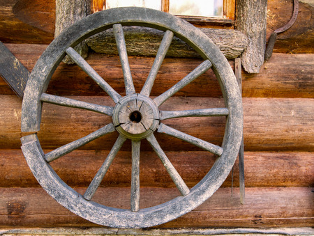 Hand spinning wheel on the wall of the old log house photo