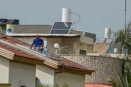 Israel. Tel Aviv. 15 APRIL 2015. View of city streets and city life. A worker repairs a roof or installs a solar panel