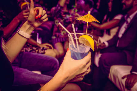 Cropped view of woman holding alcoholic cocktail in glass decorated with umbrella and lemon, peoples in the background.