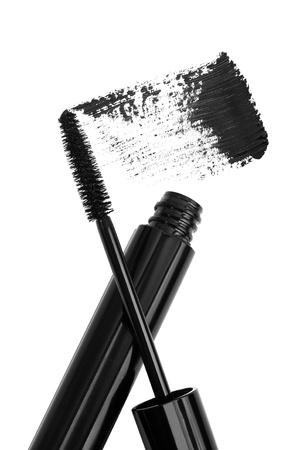 black mascara tube, brush and sample stroke isolated on white