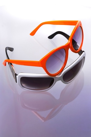 Two color sunglasses. Macro shot. Reflection background.