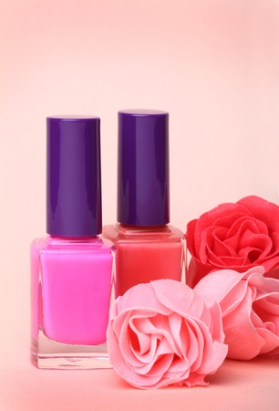 Nail polish bottles and rose flowers on pink background