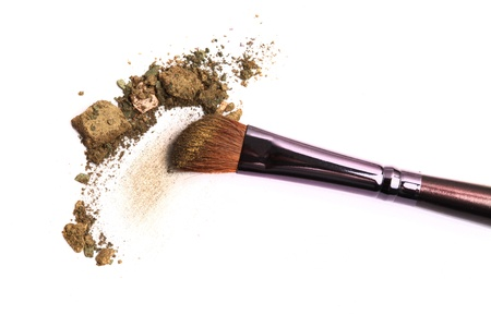 Cosmetic brush and crushed mixed color eyeshadow isolated on white