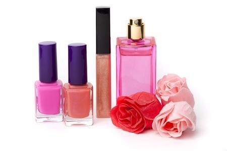 Lip gloss, perfume, nail polish bottles and rose flowers on white background