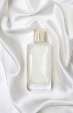 White perfume bottle on the silk.