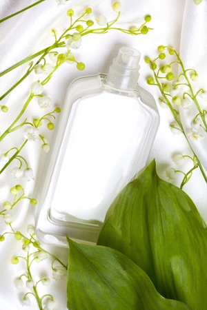 Lily of the valley and perfume bottle on white silk
