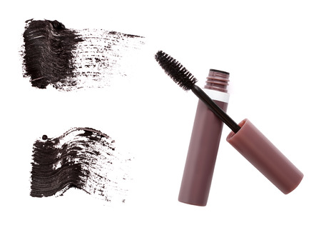 Mascara brush, tube and strokes isolated on white
