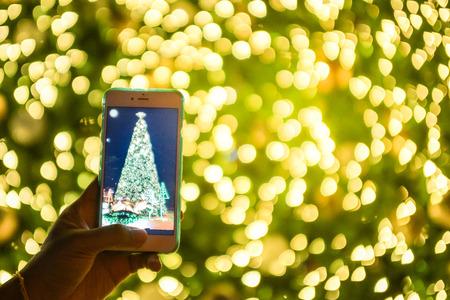 bokeh 배경으로 스마트 폰의 화면에 흐리게 크리스마스 트리 재생