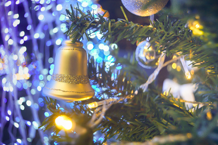 blur image of  bell and ball hang on the fake pine Christmas tree. The background is blue light and bokeh.