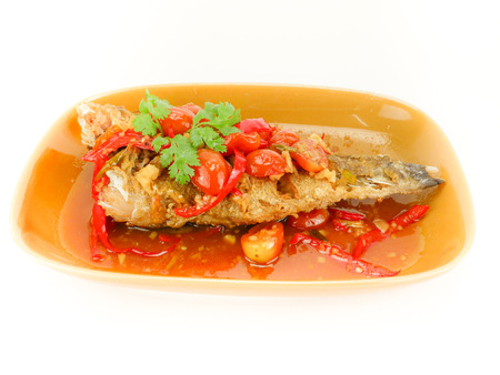 Deep Fried Fish with Chili Sauce  (Pla Rad Prik) and  herb topped on ; tomato Bell pepper garlic Tamarind Parsley . on brown dish in white background. Thai traditional food style Stock Photo