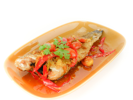 Deep Fried Fish with Chili Sauce  (Pla Rad Prik) and  herb topped on ; tomato Bell pepper garlic Tamarind Parsley . on brown dish in white background. Thai traditional food style Foto de archivo