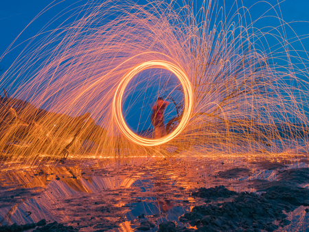 light lines of steel wool with long exposure, speed motion abstract background in the dark night with dry branch tree and reflection in water