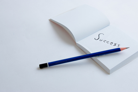 Success concept write down in a white paper book with pencil