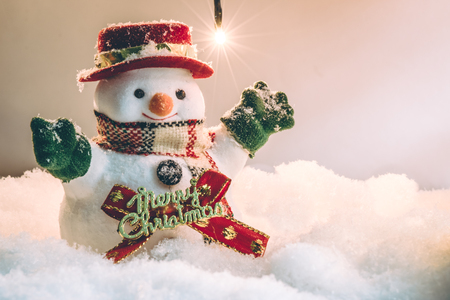 silent night: Snowman and light bulb stand among pile of snow at silent night, light up the hopefulness and happiness in Merry christmas and new year night.