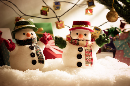 hopefulness: Snowman stand among pile of snow at silent night with a light bulb, light up the hopefulness and happiness in Merry christmas and new year night.