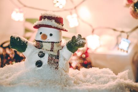silent night: Snowman stand among pile of snow at silent night with a light bulb, light up the hopefulness and happiness in Merry christmas and new year night.