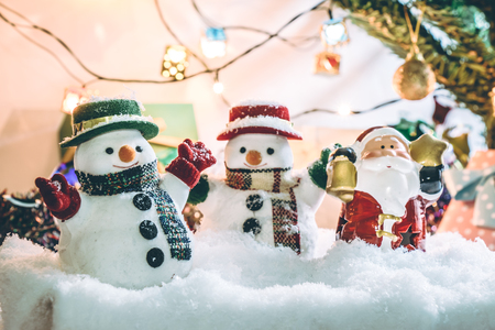 silent night: Snowman and Santa claus hold bell among pile of snow at silent night with a light bulb, light up the hopefulness and happiness in Merry christmas and new year night.