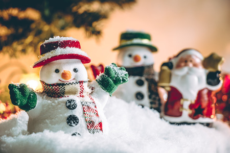 hopefulness: Snowman and Santa claus hold bell among pile of snow at silent night with a light bulb, light up the hopefulness and happiness in Merry christmas and new year night.