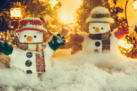 hopefulness: Snowman and snow is falling down, stand among pile of snow at silent night with a light bulb, light up the hopefulness and happiness in Merry christmas and happy new year night. Stock Photo