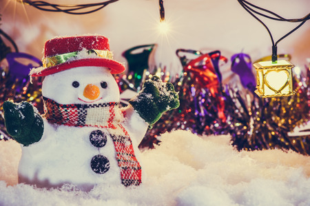 hopefulness: Snowman stand among pile of snow at silent night with a light bulb, light up the hopefulness and happiness in Merry christmas and happy new year night.