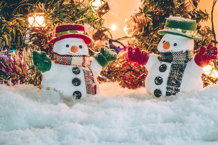 silent night: Snowman stand among pile of snow at silent night with a light bulb, light up the hopefulness and happiness in Merry christmas and happy new year night.