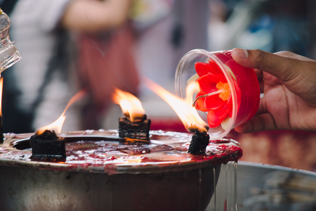 believable: Burning red flower candle at chinese shrine for making merit in chinese new year festival. Pray for New Year,Lighting incense to Buddha.
